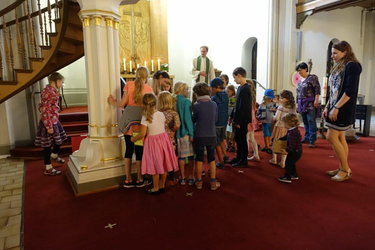 Kinder mit Pastor und Helferinnen vor dem Altar